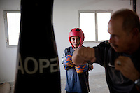 """Nasr Eddin, one of 2 coaches of the club, sketchs a hook in front of Ahmed, concentrated to the advice of the former boxer. The 10-year-old young boy wants to become an astronaut. """" I should continue boxing in stars! """", he hopes."""