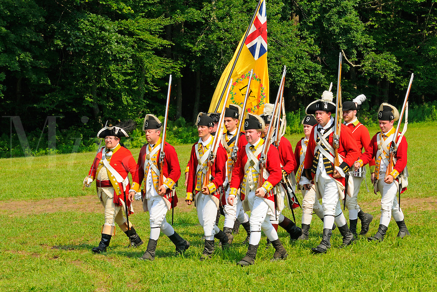 British redcoat soldiers, mostly of the Ninth Regiment of Foot, display regimental colors as they march from the battlefield during a skirmish during a Revolutionary War reenactment at the Nathan Hale Homestead, Coventry, Connecticut, USA...