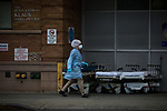 A medical worker walks past hospital beds in front of the emergency room at Maimonides Medical Center on March 28, 2020 in Brooklyn, NY.  NYC's daily death toll from the coronavirus nearly tripled from the previous 24-hour period from 85 on Friday to 222 on Saturday.  Photograph by Michael Nagle/Redux