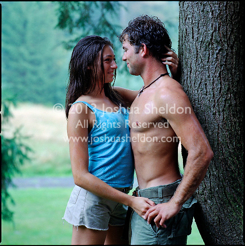 Couple embracing, leaning against a tree.