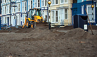 Aberystwyth, West Wales, UK. Thursday 11th February 2016<br /> A digger clears debris from Aberystwyth promenade as work continues on the the clean up after Storm Imogen battered the west Wales town.