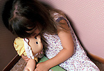 little girl huddled in corner of room clutching doll