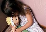 little girl huddled in corner of room clutching doll