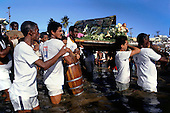 Salvador, Bahia, Brazil. Iemanja Festival; Candoble followers dressed in white carrying an offering of flowers to the sea.