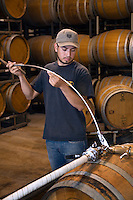Winery worker measures the level of sediment in an OAK BARREL at JOULLIAN VINEYARDS - CARMEL VALLEY, CALIFORNIA