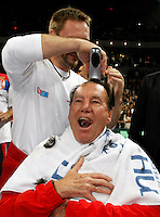 Nikola Pilic gets a celebratory haircut on the court right after the Serbian national tennis team won the Davis Cup finals against France in Belgrade Arena, Belgrade, Serbia, Sunday, December. 5, 2010. (credit & photo: Pedja Milosavljevic/SIPA PRESS)