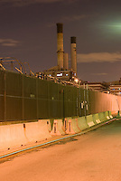 Electric Power Plant Behind Chain Link Fence and Concrete Security Barriers at Night, The Vinegar Hill neighborhood of Brooklyn, New York City, New York State, USA