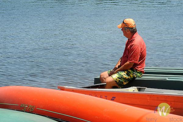 Man looking at Eagles Mere Lake. Edge Mere Dock.