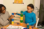 7 year old girl with mother activity building colorful wooden marble run using visual directions horizontal