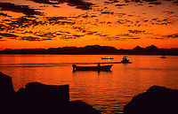 Small fishing boats in the quiet ocean at a beautifull sunset in Baja California