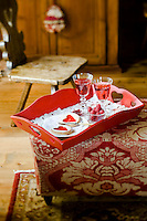 A red wooden tray with delicate cakes, fresh raspberries and rose wine on an ottoman in the living room