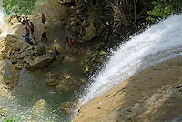 Group of people sitting on rocks and relaxing at the foot of a waterfall, Soroa Cascade, Cuba.