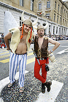 Switzerland. Canton of Neuchâtel. Neuchâtel. Grape Harvest Festival. Two men, dressed up as Astérix and Obélix the famous heros from the comic strip, during the parade. Confettis on the road. Pedestrian crossing. © 2006 Didier Ruef