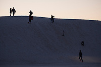 People watch the sunset and play on dunes at White Sands National Monument near Alamogordo, New Mexico, USA, on Fri., Dec. 29, 2017.