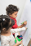 Education Preschool toddler-2s program art activity boy and girl drawing with crayons at easel