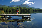 Small boy on the dock at Daicey Pond with Mt. Katahdin in the background, Baxter State Park, Maine, USA