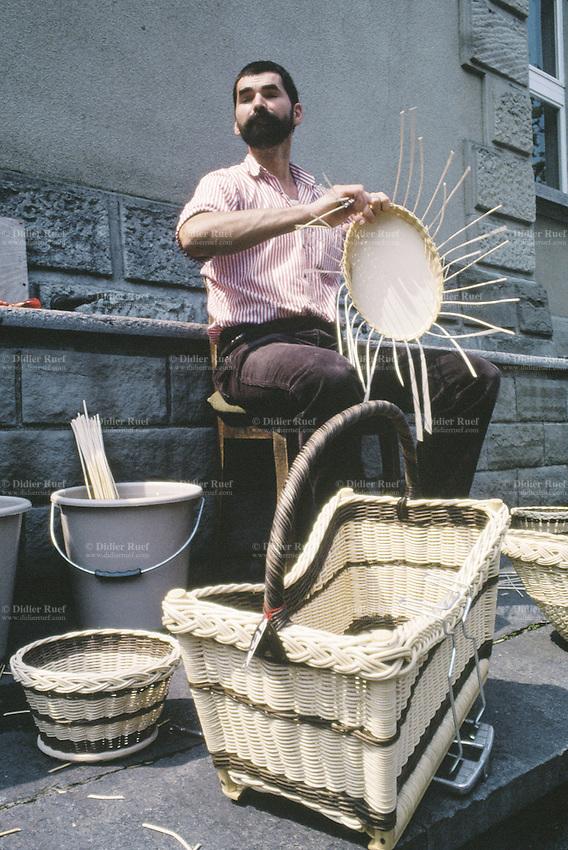 Switzerland. Zoug. Old town. Summer season. A bearded man makes wicker baskets near a water fountain. © 1989 Didier Ruef