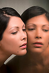 Young Hispanic woman and her mirror reflection