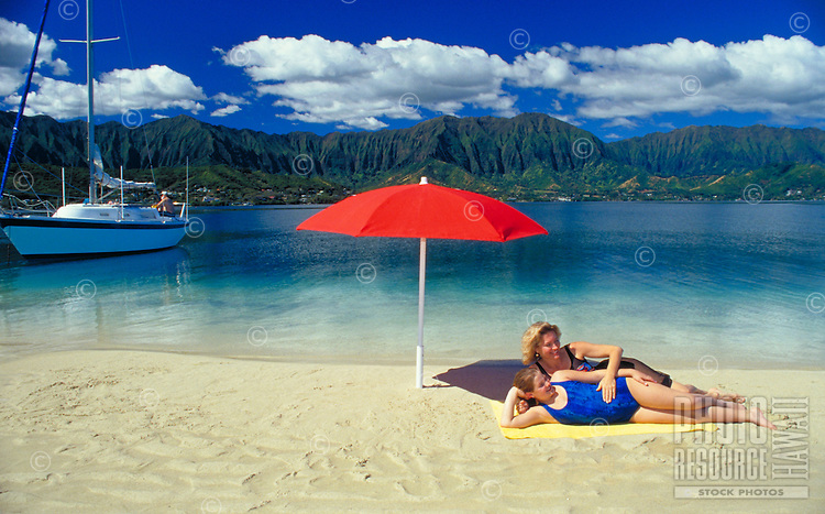 A mother and daughter relax under a red umbrella on a sandbar at Kaneohe bay on the windward side of Oahu.