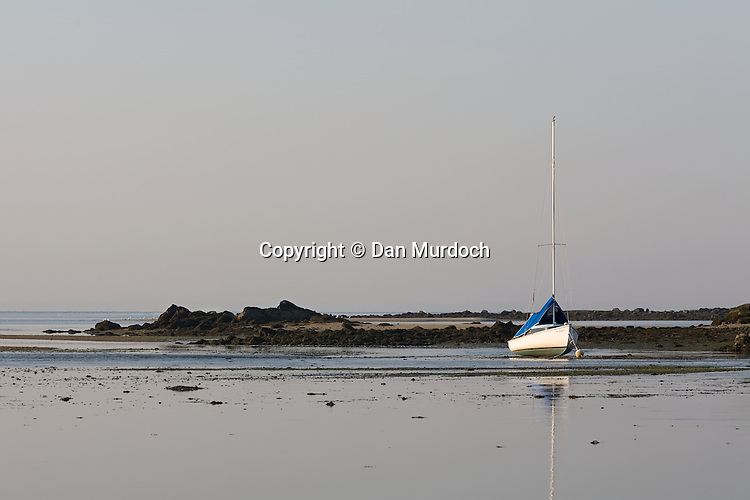 small sailboat aground at low tide