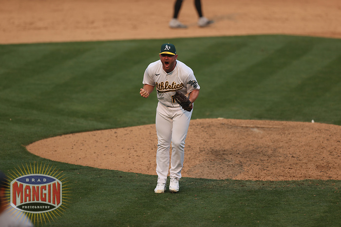 OAKLAND, CA - OCTOBER 1:  Liam Hendriks #16 of the Oakland Athletics celebrates after getting the last out against the Chicago Sox to win Wild Card Round Game Three and the payoff series at the Oakland Coliseum on Thursday, October 1, 2020 in Oakland, California. (Photo by Brad Mangin)