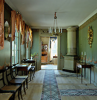 In the dining room the carpets - printed on widths of heavy linen - and the ormolu chandelier are typical features of early 19th century Swedish interiors