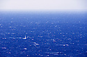 Single sailboat in the open blue ocean