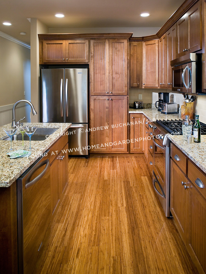 Mottled speckled granite countertops, dark stained cabinetry, hardwood floors, and stainless steel appliances in this kitchen in a builder spec home prove that small, townhouse-style houses don't have to be short on features.