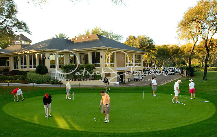 A group of golfers practice putting on a practice green in Amelia Island, FL