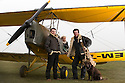 """13/03/15<br /> <br /> L/R: Tim Cox (Deputy Chief Flight Instructor), Kerry Flanagan (experience Manager) and Will Flanagan (Chief Flight Instructor), with Blue Eye Aviations' mascot, Labrador, Tess.<br /> <br /> ***FULL STORY HERE:   http://www.fstoppress.com/articles/tiger-moth-restorations/    ****<br /> <br /> You may remember spending hours toiling over Airfix models, painstakingly following intricate instructions and trying not to glue your fingers together before painting your own miniature version of one of the RAF's or Luftwaffe's finest aircraft. Then spare a thought for one man who has just helped to restore and put together one World War Two Tiger Moth and is about to start piecing together another FOUR aircraft that were discovered in bits in a barn.<br /> <br /> Sixty-year-old Colin Temple-Smith – who wears a moustache that any Wing Commander would be proud of – has spent a lifetime restoring vintage cars and motorcycles and recently quit his job as a window fitter to help re-build the five bi-planes that will become part of a growing fleet of Tiger Moths at Derbyshire based Blue Eye Aviation.<br /> <br /> Today saw the first of the fully-restored five aircraft take to the skies.<br /> <br /> """"It's just like working on old bikes and cars, although they're a lot more fragile"""" explained Colin, whose wife runs the Aviators Café at Darley Moor Airfield near Ashbourne.<br /> <br /> """"When I was a teenager I used to be a member of a modelling club, making flying models from wood and canvas. They're very similar to build – it's really just the size that's changed with these.<br /> <br /> All Rights Reserved: F Stop Press Ltd. +44(0)1335 418629   www.fstoppress.com."""