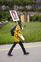 Switzerland. Canton Valais. St-Maurice. Africa Saints Pilgrimage (Pèlerinage aux Saints d'Afrique). Religious <br /> procession. An african man carries a religious drawing and takes pictures with his mobile phone while walking on a road towards St-Maurice's abbey.  2.06.13 © 2013 Didier Ruef