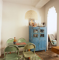 A dining room with neutral painted walls and a stone floor. Four green folding metal chairs are placed around a simple wooden table. A blue painted dresser stands against one wall.
