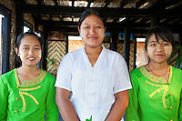 Myanmar, Burma.  Three Burmese Waitresses at Restaurant for Tourists, Inle Lake, Shan State.  They are wearing thanaka paste on their faces, a cosmetic sunscreen.