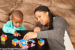 Two year old toddler boy with mother talking with her shown how puzzle goes together