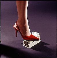 Woman's high heel shoe sitting on stack of one hundred dollar bills<br />