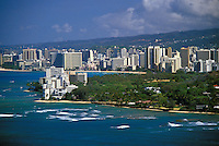 Low aerial view of Waikiki to with hotels past the Diamond head gold coast end of the coastline.