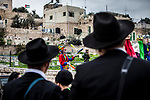 An Israeli soldier stands guard as Jewish settlers celebrate the Purim holiday in a parade at the West Bank city of Hebron Sunday March 12 2017. Purim is a Jewish holiday that commemorates the saving of the Jewish people in ancient Persia , the story is recorded in the Biblical Book of Esther. Photo by Eyal Warshavsky