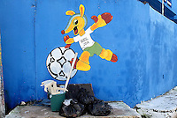 Graffiti of the World Cup mascot Fuleco painted on a wall above some rubbish in Natal, Brazil