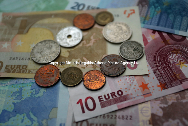A mixture of old drachma coins surrounding the map of Europe on a 50 euro paper note
