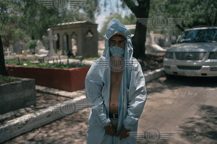A worker puts on a hazmat suit, although he is bare-chested beneath it due to the heat, before working at a burial service at the San Lorenzo Tezonco public cemetery in Iztapalapa. Some of the workers in the COVID-19 section of the cemetery are unpaid and work for tips from mourners.