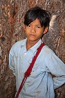 Myanmar, Burma.  Young Burmese Boy in Village near Bagan.  He has traces of thanaka paste, a cosmetic sunscreen, on his face.  Burman (Bamar) ethnic group.
