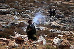 Israeli border police officers throw a tear gas grenade towards Palestinian protesters during a demonstration against Israel's controversial separation barrier in the West Bank village of Nilin, near Ramallah.  Five Palestinians were wounded today as Israeli soldiers fired rubber bullets at demonstrators protesting at the construction of a separation wall on the outskirts of Nilin, medics said.