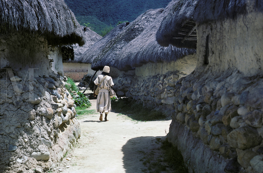 A native Arhuaco indian man walks through the village of San Sebastian, located in the Sierra Nevada de Santa Marta mountains of coastal Colombia. He wears traditional woolen clothing.