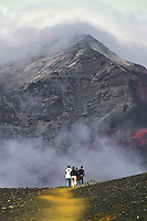 Male and female hikers heading into the cloud covered crater of HALEAKALA NATIONAL PARK on Maui in Hawaii USA