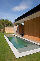 A minimal lap pool lines one of the wood-clad exterior walls of the property