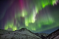 The colorful aurora arcs over the White Mountains National Recreation Area, Interior, Alaska.