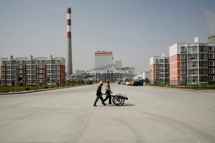 Two workers push a cart down the street at an apartment complex near a power plant in Yinchuan, Ningxia Hui Autonomous Region, China. According to the first-quarter report of the State Environmental Protection Administration (SEPA), pollution across the country has been worsening and foul air emissions are beyond acceptable limits. Pollution index in some cities is above 300. Worsening air and water pollution made cancer the top killer in China last year..19 May 2007