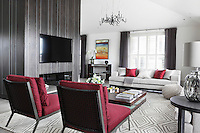 A palette of red, white and grey has been used in the living space of this London apartment