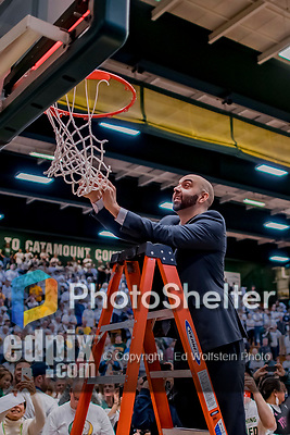 16 March 2019: University of Vermont Catamount Associate Head Coach Kyle Cieplicki, cuts himself a piece of net after a victory over the UMBC Retrievers in the America East Championship Game at Patrick Gymnasium in Burlington, Vermont. The Catamounts defeated the Retrievers 66-49, avenging their loss against the same team in last years' Championship Game. Mandatory Credit: Ed Wolfstein Photo *** RAW (NEF) Image File Available ***