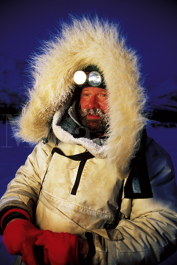 Portrait of an Iditarod musher in a fur lined heavy coat, backlit by early morning light. Alaska.